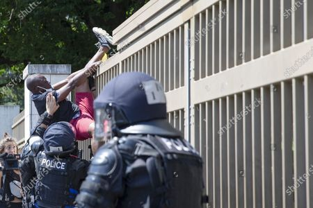 Swiss riot police intervenes against an opponent of Cameroon's President Paul Biya who protest against his presence in Geneva, attempting to enter in the UN, during a demonstration at place des Nations in front of the European headquarters of the United Nation in Geneva, Switzerland, 17 July 2021.