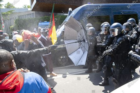 Swiss riot police use pepper spray to disperse opponents of Cameroon's President Paul Biya who protest against his presence in Geneva, attempting to enter in the UN, during a demonstration at place des Nations in front of the European headquarters of the United Nation in Geneva, Switzerland, 17 July 2021.