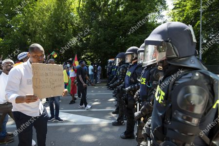 Opponents of Cameroon's President Paul Biya protest against his presence in Geneva in front of Swiss riot police, during a demonstration at place des Nations in front of the European headquarters of the United Nation in Geneva, Switzerland, 17 July 2021.