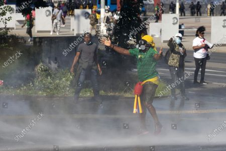 Stock Image of Swiss riot police use water cannon against opponents of Cameroon's President Paul Biya who protest against his presence in Geneva, during a demonstration at place des Nations in front of the European headquarters of the United Nation in Geneva, Switzerland, 17 July 2021.