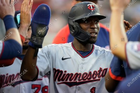 Minnesota Twins' Nick Gordon is greeted in the dugout after scoring from third on a wild pitch during the eighth inning of the second baseball game of a doubleheader against the Detroit Tigers, in Detroit