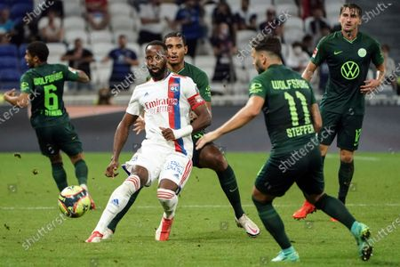 Lyon's Moussa Dembele, center, challenges for the ball with Wolfsburg' players during their friendly soccer match in Decines, near Lyon, central France