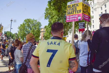 A demonstrator wears a Saka football shirt and holds a Black Lives Matter placard during the anti-racism protest. Demonstrators held speeches and took the knee outside Downing Street in solidarity with England football players; Marcus Rashford, Bukayo Saka and Jadon Sancho, following the online racist abuse the trio received after the Euro 2020 final between England and Italy.