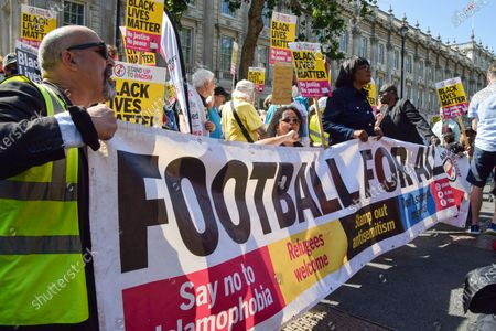Demonstrators hold a 'Football For All' banner and Black Lives Matter placards during the anti-racism protest. Demonstrators held speeches and took the knee outside Downing Street in solidarity with England football players; Marcus Rashford, Bukayo Saka and Jadon Sancho, following the online racist abuse the trio received after the Euro 2020 final between England and Italy.