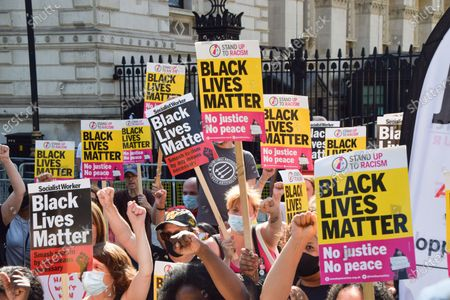 Demonstrators gesture while holding Black Lives Matter placards during the anti-racism protest. Demonstrators held speeches and took the knee outside Downing Street in solidarity with England football players; Marcus Rashford, Bukayo Saka and Jadon Sancho, following the online racist abuse the trio received after the Euro 2020 final between England and Italy.