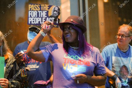 """Philly activist legend Saj """"Purple"""" Blackwell holds up the Black Power Solidarity Fist during a candlelight vigil for Civil Rights hero John Lewis in Philadelphia, PA, on July 17, 2021."""