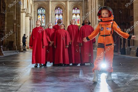 It's a Walk on the Moon at Peterborough Cathedral. A virtual moonscape by the artist Peter Walker using NASA images creates a copy of the moon underfoot.. Pictured Bobbie Crooks, the Astronaut with Peterborough Cathedral Coristers, standing on the Art Installation the day before if opens.Peterborough Cathedral, Peterborough.