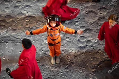 Stock Image of It's a Walk on the Moon at Peterborough Cathedral. A virtual moonscape by the artist Peter Walker using NASA images creates a copy of the moon underfoot.. Pictured Bobbie, the Astronaut with Peterborough Cathedral Coristers, standing on the Art Installation the day before if opens.Peterborough Cathedral, Peterborough.
