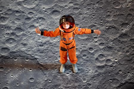 It's a Walk on the Moon at Peterborough Cathedral. A virtual moonscape by the artist Peter Walker using NASA images creates a copy of the moon underfoot.. Pictured Bobbie, the Astronaut standing on the Art Installation the day before if opens.Peterborough Cathedral, Peterborough.