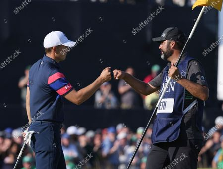 Stock Picture of United States' Jordan Spieth bumps fists with his caddie Michael Greller on the 18th green after completing his final final round of the British Open Golf Championship at Royal St George's golf course Sandwich, England