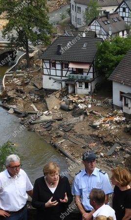 German Chancellor Angela Merkel (2-L) and Rhineland-Palatinate State Premier Malu Dreyer (R) speak as they stand on a bridge during their visit in the flood-ravaged areas in Schuld near Bad Neuenahr-Ahrweiler, western Germany, 18 July 2021. After days of extreme downpours causing devastating floods in Germany and other parts of western Europe the death toll has risen to 156 in Germany, police said 18 July, bringing the total to at least 183 fatalities from the disaster in western Europe.