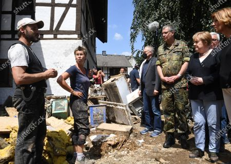 German Chancellor Angela Merkel (2-R) and Rhineland-Palatinate State Premier Malu Dreyer (R) talk to residents during their visit in the flood-ravaged village of Schuld near Bad Neuenahr-Ahrweiler, western Germany, 18 July 2021. After days of extreme downpours causing devastating floods in Germany and other parts of western Europe the death toll has risen to 156 in Germany, police said 18 July, bringing the total to at least 183 fatalities from the disaster in western Europe.