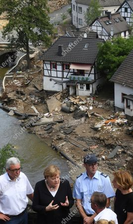 German Chancellor Angela Merkel, 2nd left, and Rhineland-Palatinate State Premier Malu Dreyer, right, talk as they stand on a bridge overlooking the devastation in the flood-damaged village of Schuld near Bad Neuenahr-Ahrweiler, Germany, . After days of extreme downpours causing devastating floods in Germany and other parts of western Europe the death toll has risen