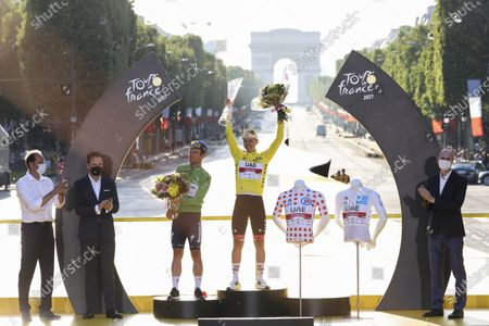 Tour de France winner Slovenia's Tadej Pogacar, wearing the overall leader's yellow jersey, and Britain's Mark Cavendish, wearing the best sprinter's green jersey, celebrate on the podium after the twenty-first and last stage of the Tour de France cycling race over 108.4 kilometers (67.4 miles) with start in Chatou and finish on the Champs Elysees in Paris, France