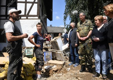 Stock Image of German Chancellor Angela Merkel, 2nd right, and Rhineland-Palatinate State Premier Malu Dreyer, right, talk to residents during their visit to the flood-damaged village of Schuld near Bad Neuenahr-Ahrweiler, Germany, . After days of extreme downpours causing devastating floods in Germany and other parts of western Europe the death toll has risen