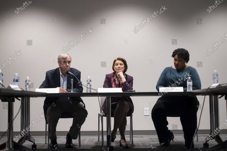 Sen. Jeff Merkley, D-Ore., from left, Sen. Amy Klobuchar, D-Minn., and former Georgia State Rep. Stacey Abrams listen to voters during a roundtable in Smyrna, Ga., on
