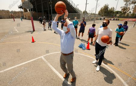 """Stock Photo of Congressman Adam Schiff takes a free throw shot with Nick Melvoin, Los Angeles Unified Board Vice President, and students as they are coached by former NBA players Craig Smith and Jason Collins on the basketball court during Fairfax High School's """"Field Day"""" event to launch the Ready Set volunteer recruitment campaign to highlight the nationwide need for mentors and tutors, to prepare the country's public education students for the upcoming school year. U.S. Secretary of Education Miguel Cardona attended as the event coincides with National Summer Learning Week, where Secretary Cardona is highlighting the importance of re-engaging students and building excitement around returning to in-person learning this fall. high school, with interim LAUSD superintendent and others. Fairfax High School on Wednesday, July 14, 2021 in Los Angeles, CA."""