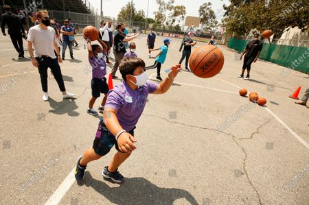 """Students Max Ananian, 9, and Khaedon Poole, 9, are assisted by Los Angeles Unified Board Vice President Nick Melvoin, left, as they are coached by former NBA players Craig Smith and Jason Collins on the basketball court during Fairfax High School's """"Field Day"""" event to launch the Ready Set volunteer recruitment campaign to highlight the nationwide need for mentors and tutors, to prepare the country's public education students for the upcoming school year. U.S. Secretary of Education Miguel Cardona attended as the event coincides with National Summer Learning Week, where Secretary Cardona is highlighting the importance of re-engaging students and building excitement around returning to in-person learning this fall. high school, with interim LAUSD superintendent and others. Fairfax High School on Wednesday, July 14, 2021 in Los Angeles, CA."""
