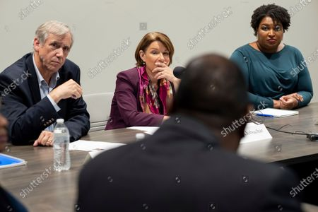 Sen. Jeff Merkley, left, D-Ore.; Sen. Amy Klobuchar, D-Minn., and former Georgia state Rep. Stacey Abrams, right, listen to people talk about their experiences in voting, in Smyrna, Ga