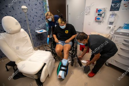 Jose Morales, right, helps his daughter Sandy Vazquez, 30, middle, get back into her wheelchair following a doctors appotinment at on Wednesday, June 9, 2021 in Los Angeles, CA. Sandy is a patient at the Wound Healing and Hyperbaric Center at MLK Community Healthcare. She recently has foot surgery and her father has brought her in for a followup appointment. (Francine Orr / Los Angeles Times)