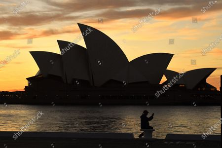 A man sits in front of the Sydney Opera House at dawn in Sydney, New South Wales, Australia, 19 July 2021. The stay-at-home orders for coronavirus-hit Greater Sydney and surrounds have been tightened with non-essential retail to close and all construction paused until 30 July.