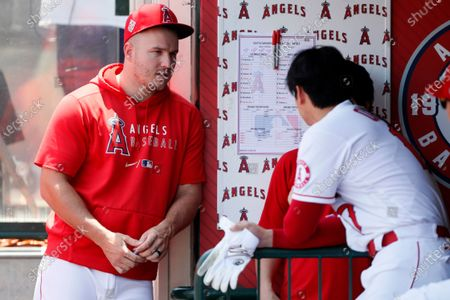 Los Angeles Angels' Mike Trout, left, talks with Shohei Ohtani in the dugout during the first inning of a baseball game against the Seattle Mariners in Anaheim, Calif