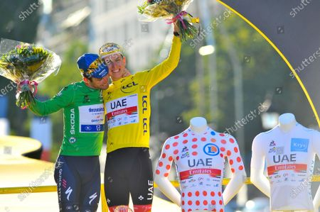 Mark Cavendish (GBR) in the points classification green jersey hugs Tadej Pogacar (SLO) with his general individual classification yellow jersey, best climber classification polka-dot jersey and best young rider classification white jersey during the final podium ceremony after the twenty-first stage of Tour de France cycling race over 108.4 kilometers (67.3 miles) with start in Chatou and finish in Paris, France, Sunday, July 18, 2021.