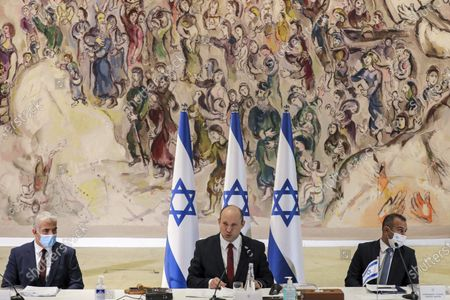 Israeli Prime Minister Naftali Bennett, center, chairs the weekly cabinet meeting at the Knesset, while Alternate Prime Minister and Foreign Minister Yair Lapid, left, looks on in Jerusalem