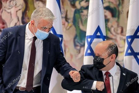Israeli Prime Minister Naftali Bennett, right, elbow-bumps Alternate Prime Minister and Foreign Minister Yair Lapid, left, before the start of the weekly cabinet meeting at the Knesset in Jerusalem