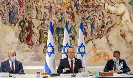 Israeli Prime Minister Naftali Bennett, center, chairs the weekly cabinet meeting at the Knesset in Jerusalem, while Alternate Prime Minister and Foreign Minister Yair Lapid, left, looks on