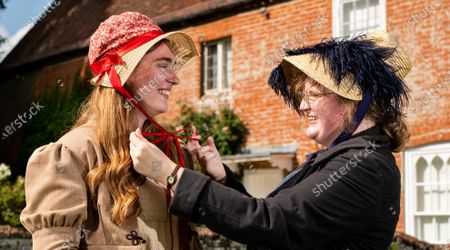 Stock Photo of Museum assistant Rebecca Wood and poet-in-residence Ellora Sutton wear traditional regency dresses and bonnets paired with trainers and boots to encourage DIY regency fashion during preparations ahead of the 204th anniversary of the death of Jane Austen at the Jane Austen's House Museum in Chawton near Alton, Hants.   Across the weekend the Jane Austen House Museum will be hosting an array of events to mark the anniversary of the death of Jane Austen on July 18th, including a guided tour through the village of Chawton, Mrs Eltonâ€s Strawberry Picnic in the gardens of the house and a Dress Up Day, where members of the public are invited to try and dress in regency fashion.