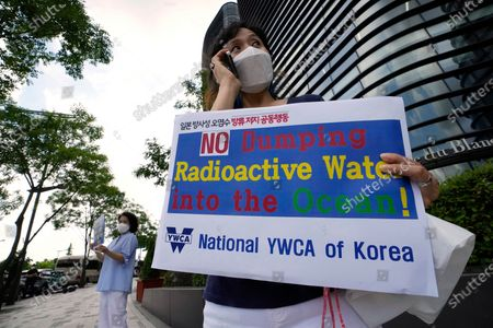 Members of the National YWCA of Korea stand to oppose South Korean President Moon Jae-in's possible visit to Japan, in front of a building which houses Japanese embassy in Seoul, South Korea, . Moon has decided not to visit Japan for the Tokyo Summer Olympics, citing a failure to set up a summit with Japan's prime minister that would produce meaningful results in improving relations