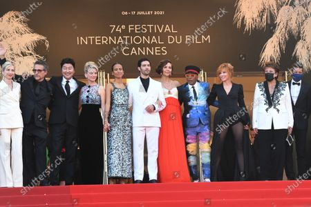 """(L-R) Jury members Kang-Ho Song, Maggie Gyllenhaal, Jessica Hausner, Mati Diop, Jury President Spike Lee, Mélanie Laurent, Tahar Rahim, Mylene Farmer and Kleber Mendonça Filho attend the final screening of """"OSS 117: From Africa With Love"""" and closing ceremony during the 74th annual Cannes Film Festival on July 17, 2021 in Cannes, France"""