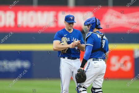 Toronto Blue Jays starting pitcher Ross Stripling, left, meets with catcher Reese McGuire on the mound during the first inning of a baseball game against the Boston Red Sox, in Buffalo, N.Y