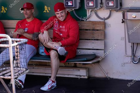 Los Angeles Angels' Mike Trout, right, sits in the dugout before a baseball game between the Oakland Athletics and the Angels in Oakland, Calif