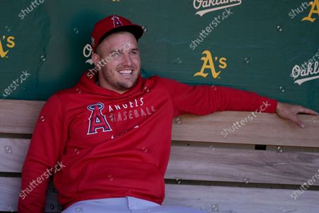 Injured Los Angeles Angels' Mike Trout sits in the dugout before a baseball game between the Oakland Athletics and the Angels in Oakland, Calif