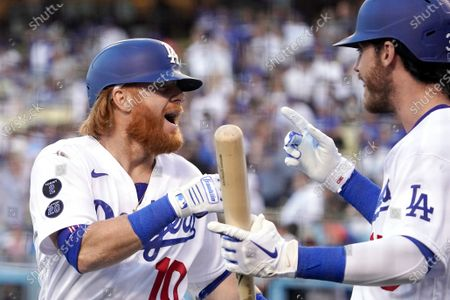 Los Angeles Dodgers' Justin Turner, left, celebrates his solo home run with Cody Bellinger during the first inning of a baseball game against the San Francisco Giants, in Los Angeles