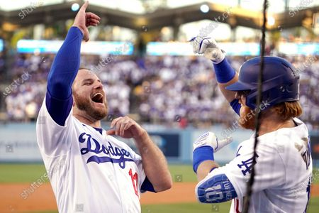Los Angeles Dodgers' Justin Turner, right, celebrates his solo home run with Max Muncy during the first inning of a baseball game against the San Francisco Giants, in Los Angeles