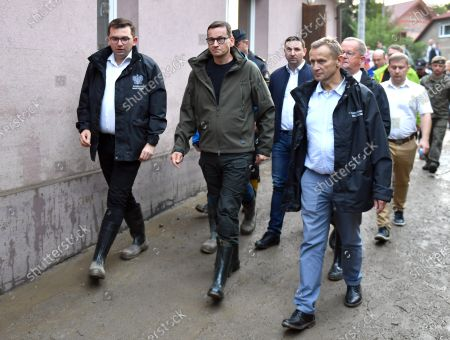 Prime Minister Mateusz Morawiecki (2L), the Governor of Malopolska, Lukasz Kmita (L), along with other officials take a walk to investigate the  damage caused by the flash flood in Glogoczów. Aftermath of flash flood in Glogoczow near Kraków.