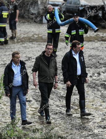 Stock Photo of Prime Minister Mateusz Morawiecki (2L) and the Governor of Malopolska, Lukasz Kmita (R), take a walk to investigate the  damage caused by the flash flood in Glogoczów in Malopolska. Aftermath of flash flood in Glogoczow near Kraków.