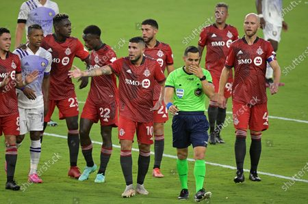 Toronto FC midfielder Alejandro Pozuelo (10) and midfielder Michael Bradley (4) argue a call during the first half of an MLS soccer match against Orlando City, in Orlando, Fla