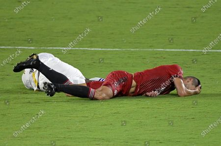 Orlando City forward Daryl Dike, left, and Toronto FC defender Omar Gonzalez (44) lie on the pitch after colliding while going for a header during the second half of an MLS soccer match, in Orlando, Fla