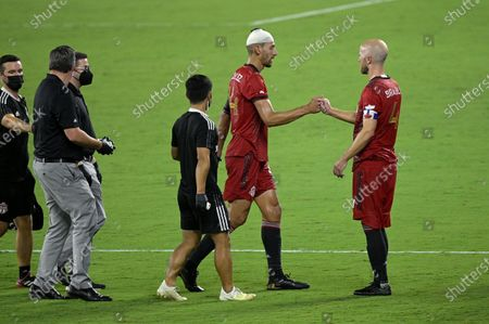 Toronto FC defender Omar Gonzalez (44) is helped off the pitch by midfielder Michael Bradley (4) after colliding with an Orlando City player during the second half of an MLS soccer match, in Orlando, Fla