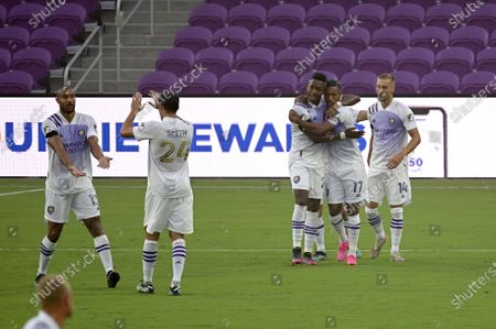Orlando City forward Nani (17) is congratulated by midfielder Andres Perea and forward Silvester van der Water (14) after Nani scored a goal during the first half of an MLS soccer match against Toronto FC, in Orlando, Fla