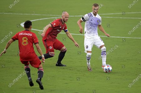 Orlando City forward Silvester van der Water, right, controls a ball between Toronto FC midfielder Mark Delgado (8) and midfielder Michael Bradley, center, during the first half of an MLS soccer match, in Orlando, Fla