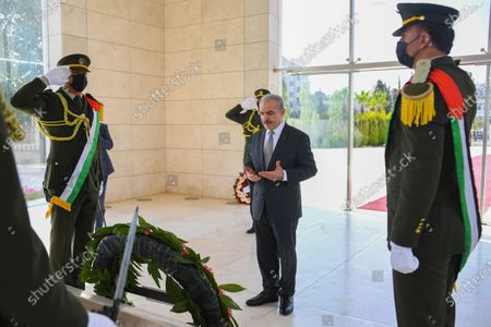 Palestinian Prime Minister Mohammad Ishtayeh lays a wreath on the grave of late Palestinian leader Yasser Arafat, on the first day of Eid al-Fitr in the West Bank city of Ramallah on July 20, 2021. Photo by Prime Minister Office