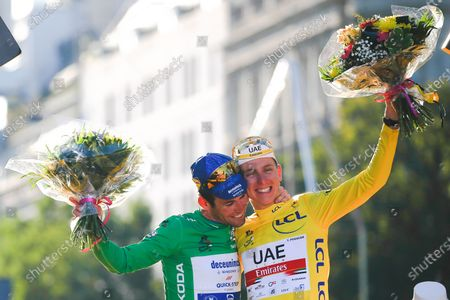 Winner Team UAE Emirates' Tadej Pogacar (R) of Slovenia celebrates his overall leader yellow jersey and Team Deceuninck QuickStep's Mark Cavendish (L) of Great Britain celebrates his green jersey of the best sprinter on the podium at the end of 21th and last stage of the 108th edition of the Tour de France cycling race, 108 km Chatou and Paris between Champs-Eli Ysees