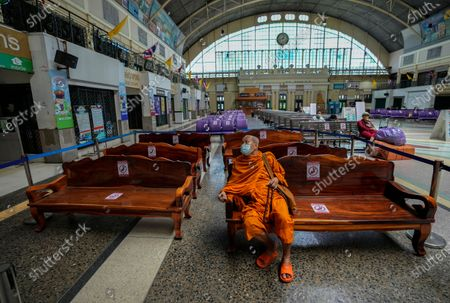 Buddhist monk wearing a face mask to help curb the spread of the coronavirus sits on a bench in the Hua Lamphong Railway Station in Bangkok, Thailand