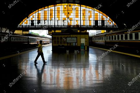 Worker wearing a face mask to help curb the spread of the coronavirus walks across the platform at the 104 year old Hua Lamphong Railway Station in Bangkok, Thailand