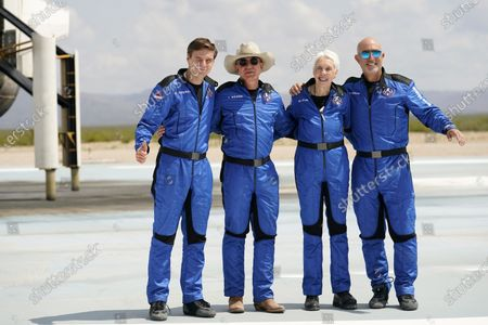Oliver Daemen, from left, Jeff Bezos, founder of Amazon and space tourism company Blue Origin, Wally Funk and Bezos' brother Mark pose for photos in front of the Blue Origin New Shepard rocket, left rear, after their launch from the spaceport near Van Horn, Texas